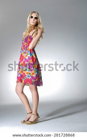 Beautiful fashion model in fashion clothes with sunglasses isolated gray background