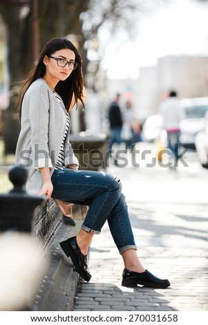 Beautiful fashion model in glasses sits