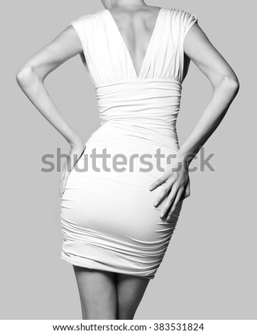 Beautiful fashion model in short white dress from behind isolated on gray background.