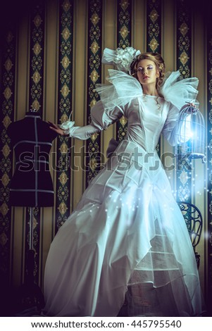 Beautiful fashion model in the refined white dress and mannequin. Vintage style. Art project. Haute Couture. - stock photo