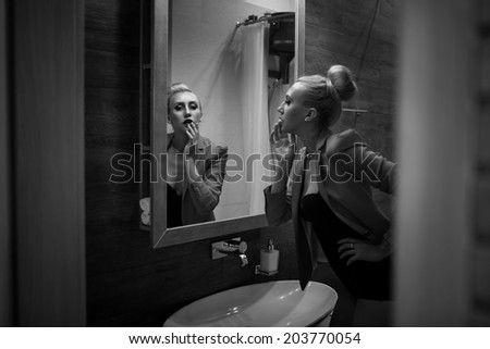 beautiful fashion model looking into the mirror  - stock photo