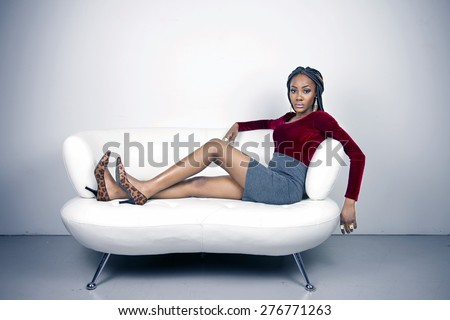 Beautiful fashion model on a white couch