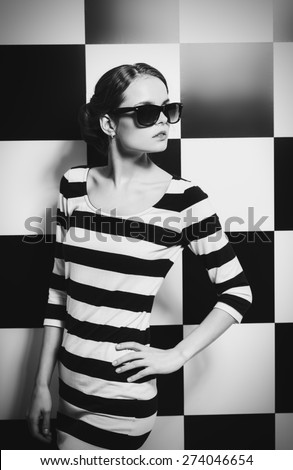 Beautiful fashion model posing in dress in black and white stripes on a background of black and white squares. Beauty, fashion concept. Black-and-white photo. - stock photo