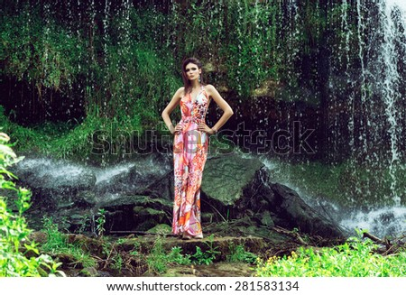 Beautiful fashion model posing in front of the waterfall - stock photo