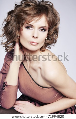 Beautiful fashion model posing in studio on gray background. - stock photo