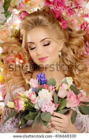 Beautiful fashion model. Sensual bride. Woman with wedding dress, hair and make up. Sweet flowers background. Blue eyes. Natural manicure. Beauty spring girl with bouquet of flowers in hands - stock photo