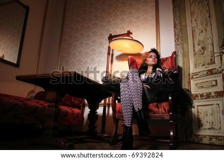 Beautiful fashion model sitting on a luxury sofa - stock photo