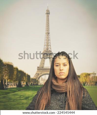 Beautiful fashion model standing against Eiffel tower - stock photo