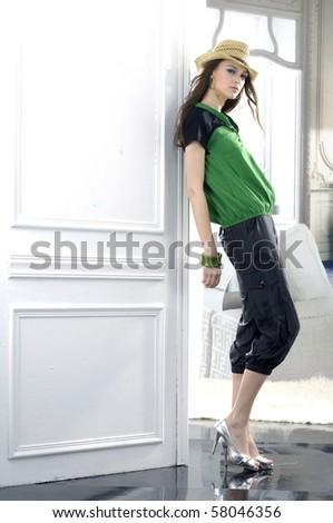 Beautiful fashion model wearing hat posing in the studio - stock photo