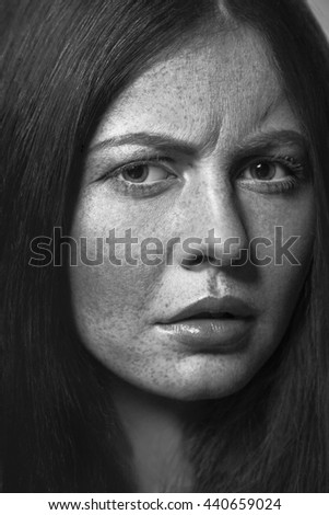 Beautiful fashion model with freckles, makeup and dark hairstyle.  Black and white photography.
