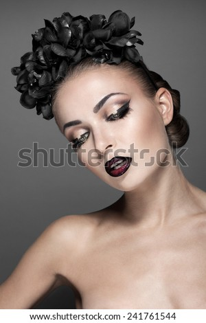 Beautiful fashion model with perfect skin posing topless with great makeup, mascara, lipstick, eyelashes, eyebrows hairstyle and black flower in her long hair - stock photo