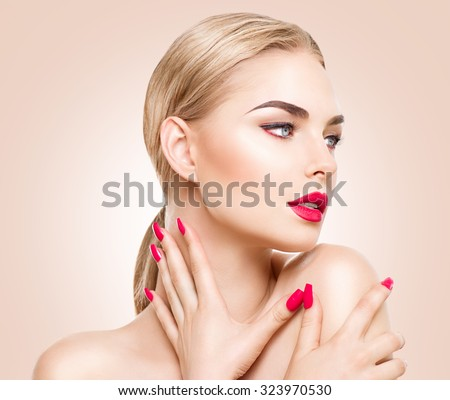Beautiful fashion model woman with perfect makeup, red lips and nails, blond hair. Red lipstick and manicure. Portrait of glamour girl with bright makeup over beige background. Beauty female face - stock photo