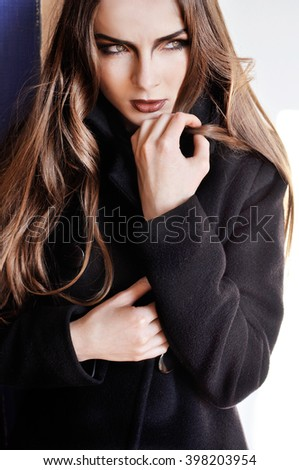 Beautiful fashion portrait of elegant caucasian girl in black coat with dark evening make-up and long hair. Perfect street fashion. Facial expression of aggression and frustration. Outdoors - stock photo