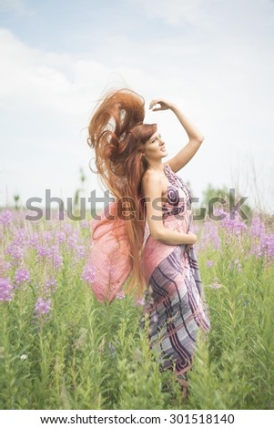 Beautiful fashion redhead woman with flying redhead long hair is wearing nice colorful sari dress Cute girl have fan on green summer field with purple blooming Sally fresh flowers Blossoming meadow - stock photo
