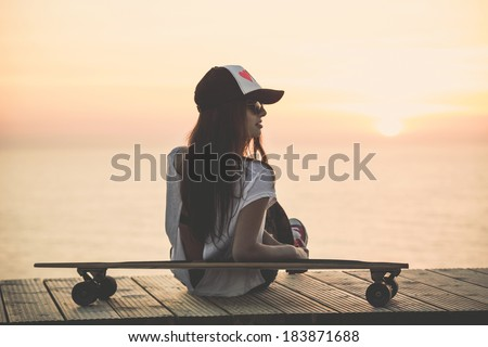 Beautiful fashion skater girl posing with  a skate board - stock photo