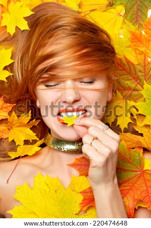 Beautiful fashion style happy fall woman smiling joyful holding autumn yellow maple leaf in mouth lying on colorful fall forest leaves background - stock photo