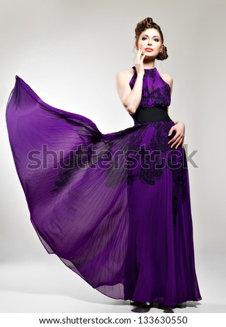 Beautiful fashion woman in purple long dress  hairstyle with pigtails design, poses at studio - stock photo