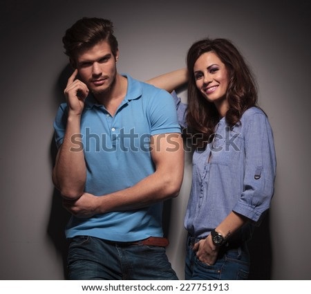Beautiful fashion woman leaning on her lover while he is holding his finger to his cheekbones. Against a grey wall.