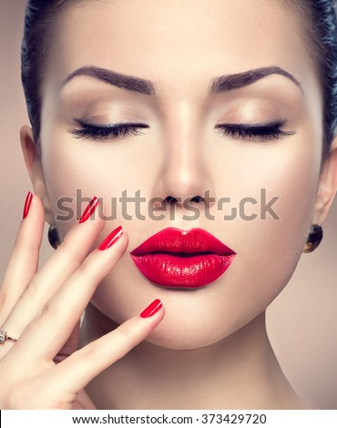 Beautiful Fashion woman model face portrait with red lipstick and red nails. Glamour girl with bright makeup. Beauty female. Perfect skin and make up. Red lips and nail polish - stock photo