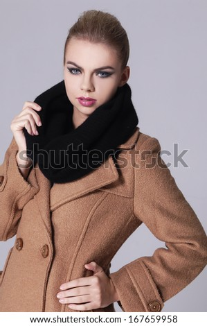 Beautiful fashion woman posing with a coat and scarf on gray background - stock photo