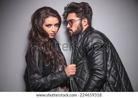 Beautiful fashion woman pulling her boyfriends jacket while looking at the camera. On grey background. - stock photo