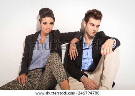 Beautiful fashion woman sitting next to her boyfriend, leaning her arm on his shoulder while he is looking away.