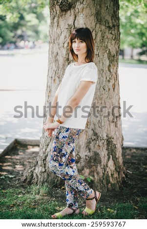 Beautiful fashion woman wearing white chiffon blouse and colorful pants posing in a park