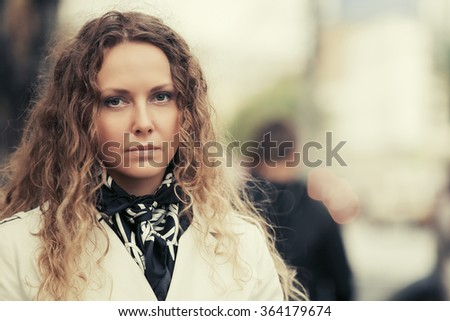 Beautiful fashion woman with long curly hairs in white coat outdoor - stock photo