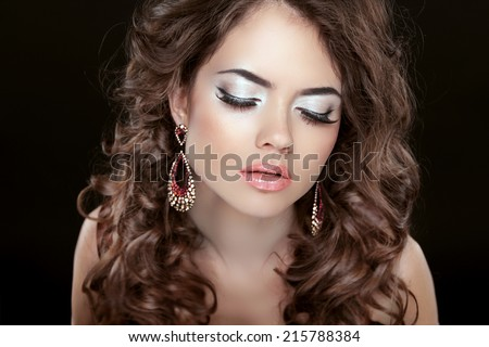Beautiful fashion woman with makeup, long wavy hair and earrings isolated on black background.