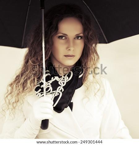 Beautiful fashion woman with umbrella in the rain - stock photo