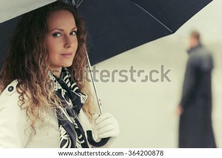Beautiful fashion woman with umbrella on city street - stock photo