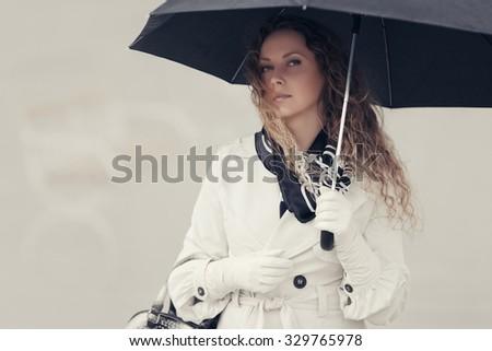 Beautiful fashion woman with umbrella walking on the city street - stock photo