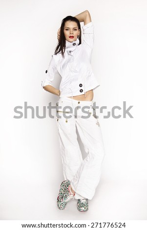Beautiful fashion young woman in white jacket and pants standing in studio on white background - stock photo