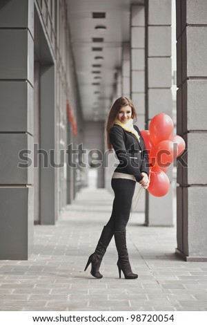 Beautiful fashion young woman with bunch of red baloons - stock photo