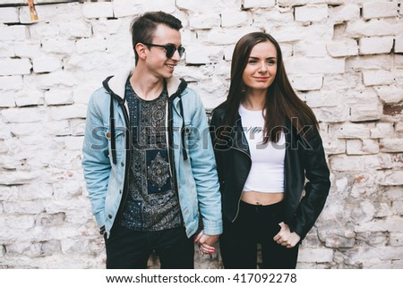Beautiful fashionable and stylish couple posing near the wall, smiling and kissing.