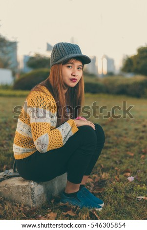 Beautiful fashionable Asian lady with brown colored hair wearing yellow cardigan and cap sitting on grass in Abu Dhabi Corniche parks