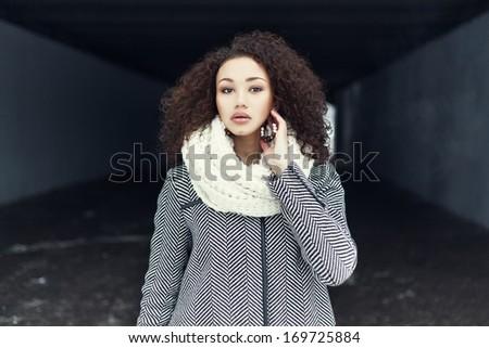 Beautiful fashionable black girl posing in a winter coat - stock photo