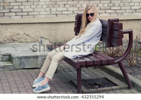 beautiful fashionable blonde woman on a bench - stock photo