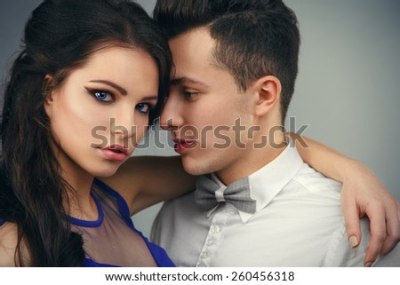 beautiful fashionable couple in the studio. beautiful fashionable couple in the studio.Portrait of glamour sexy couple in love posing in elegance clothes. - stock photo