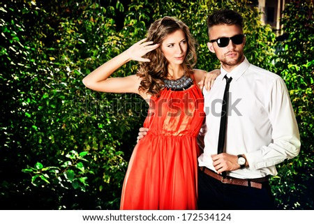 Beautiful fashionable couple standing outdoor. - stock photo
