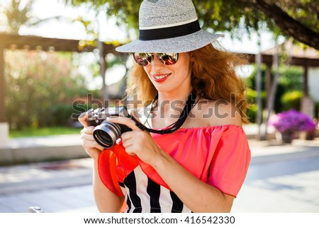 Beautiful fashionable girl happy red-haired hipster traveler, making photos in the park, holding a camera in hand, in sunglasses, a hat, a bright fashionable clothes, summer style, sport casual  - stock photo