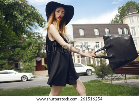 Beautiful fashionable girl in a hat and a bag in her hands, walking through the downtown - stock photo