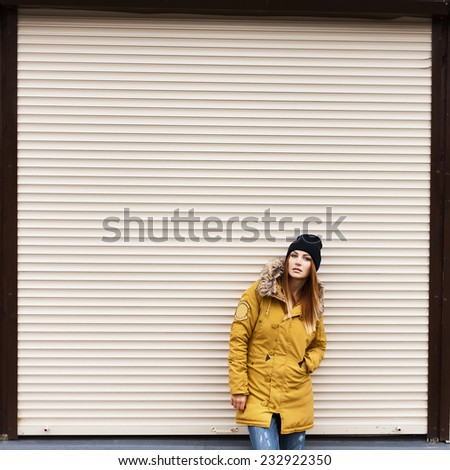 Beautiful fashionable girl in a jacket and hat in autumn on a background of a wall - stock photo
