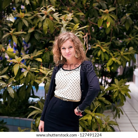 Beautiful fashionable girl on a background of plants