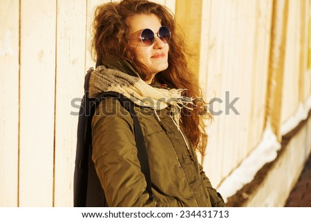 Beautiful fashionable girl posing with glasses on a sunny day near the wall