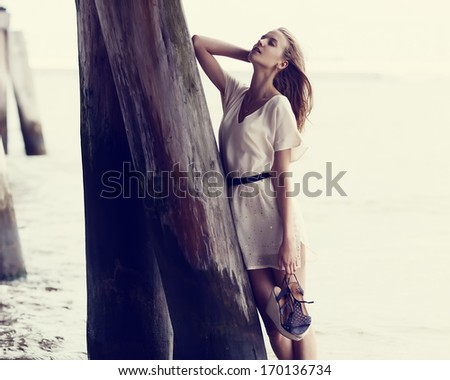 Beautiful fashionable girl standing near the pier in water in a dress with shoes in hand - stock photo