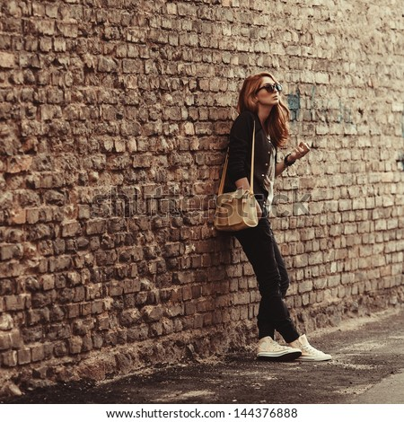 Beautiful fashionable girl stands near the brick wall with a cigarette