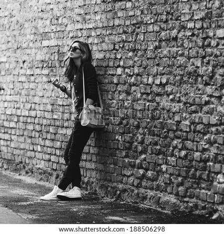 Beautiful fashionable girl stands near the brick wall with a cigarette , black and white - stock photo