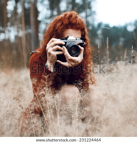 Beautiful fashionable hipster girl - photographer - stock photo