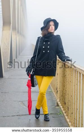 Beautiful fashionable lady walking on bridge on misty autumn day. - stock photo